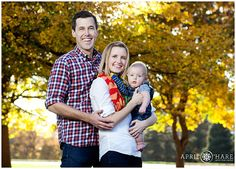 A cute young family with a 5 month old son stand underneath golden autumn trees at Cheesman Park in Denver Colorado. - April O'Hare Photography http://www.apriloharephotography.com #offcameraflash #cheesmanpark #denverfamily #DenverPhotographer #ColoradoFamilyPics
