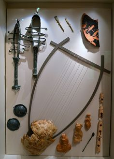 Musical instruments from Ambracia | Including a tortoise-shell (with reconstructed lyre), bronze sistra and cymbals, bone flute and plectra, terracotta figurines of flute-players (including Pan), and an Attic Red Figure sherd depicting Apollo(?). From Ambracia (modern Arta). Archaeological Museum of Arta, Epirus, Greece