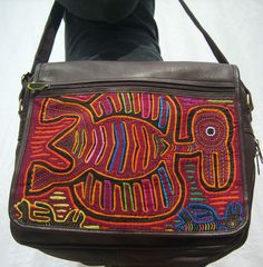 Handcrafted, Fair-Trade Leather and Mola lap top bag.This is a beautiful shoulder bag handmade in Colombia using high quality leather and colorful Mola fabrics sourced from indigenous artisans. Made by the Kuna Indians of northern Colombia, the Mola is a textile art form unique to them and their textiles are incorporated into a variety of wearable art such as shoes, wallets, and purses. These products are made by a family run fair-trade business in Colombia.