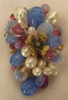 LOUIS ROUSSELET FRANCE pin with hand-wired opalescent, blue and cranberry art poured glass beads, center flower motif and lustrous faux pearls in a gold plated setting.
