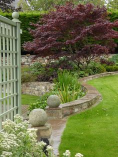 Stone balls, trellis and curved wall with mowing edge - Goose Green Design