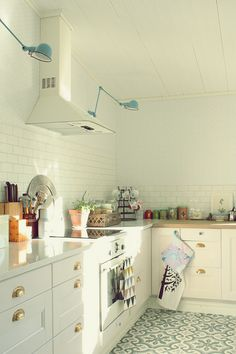 patterned tile floor in kitchen, modern lights, brass hardware, white cabinets, white tile, Scandinavian design