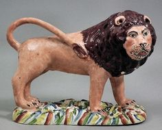 A late 18th/early 19th Century Staffordshire pearlware figure of a lion, on moulded oval base, 7.25ins overall x 5.5ins high