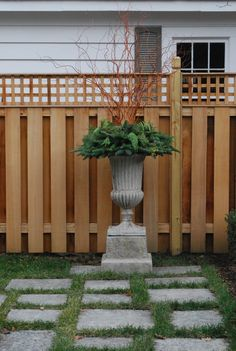 Privacy fence. Decorative lattice. Sculptural pot. Grass and stepping stone patio.