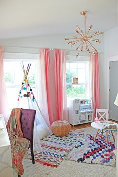 Bohemian playroom with layered rugs, Moroccan leather pour, and a modern Eames style play table. And check out that sputnik chandelier!