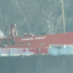 The H. Lee White stuck in the ice on the St. Clair River in Algonac, Michigan (Jan 2015) being assisted by two Canadian Coast Guards.  The Sameul Risley coming up on the side of the freigher breaking up the ice