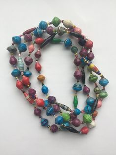 """This unique, long, multi-color beaded necklace is made from recycled paper beads, handmade by women in Kisubi, Uganda. Necklaces measure 64"""" - 68"""" long and beads are .75"""" inches in diameter. Necklace can be worn long, doubled, or tripled for multiple looks. Indicate the dominant color preferred (blue, purple, red, or white), which is indicated by the small, faceted glass beads.  ***  All Paper Bead jewelry is made by a collective of women in Kisubi, Uganda, purchased in support of Bright…"""