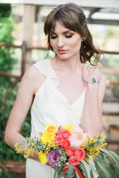 Colorful Boho Mexican Fiesta Wedding. Dress: Bella Bridesmaids Venue: Tremaine Ranch Florals: Kate Mellow of Bloom & Blueprint Photography: Denise Karis  Model: Katie from Sift Bakehouse Bouquet: beatrice gold and juliete peach rose gardens, light orange spray roses, daffodils, rose canela, acacia and yarrow tied in multi colored ribbons.