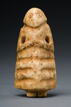 """Mesopotamian Stone Votive Figure, 3rd millennium BCE. """"Votive statues in an attitude of prayer originated in Mesopotamia at the beginning of the third millenium BC. They were placed in temples to represent the donor in perpetual prayer before the gods. As this small figure is pierced, it may have been worn as an amulet."""""""