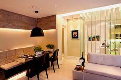 """Uma divisória de vidro """"separa"""" a sala e o quarto desta quitinete. Outra solução interessante para ganhar espaço é a mesa com banco encostado na parede.Projeto Camila Klein."""