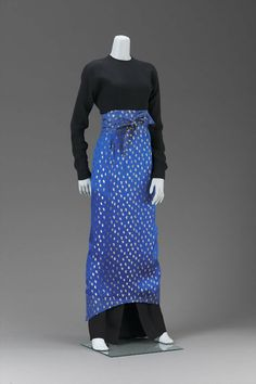 Geoffrey Beene Long, black sponge crepe dress with attached blue silk satin apron brocaded with gold and apron strings quilted with gold thread.