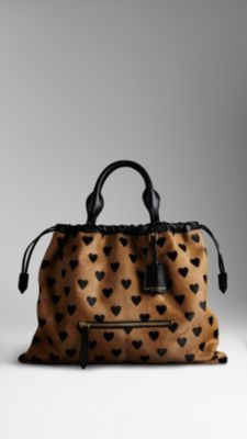 I WANT! Burberry's 'Little Crush' bag -A soft calfskin tote bag in a heart print design. Fastened with a leather drawcord, the style references classic outerwear closures.The relaxed shape is complemented by hand-stitched leather handles, a detachable shoulder strap and polished metal hardware.