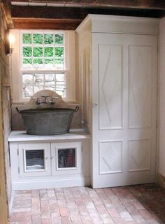 galvanized steel washtub as sink in laundry room. washe and drye stacked in closet be washtub