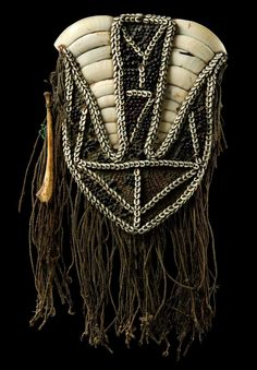 Papua New Guinea | Chest ornmanet with shield-shaped rotan plait with two gap-like cut-outs, which are filled with boar tusks, the corpus spread with resin and indented abrus beans, sewn with strings of nassa snails, twisted cord material around the rim | 900€ ~ Sold