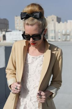Flowered dress with beige trench, topped with a cute black bow at the top of her chignon