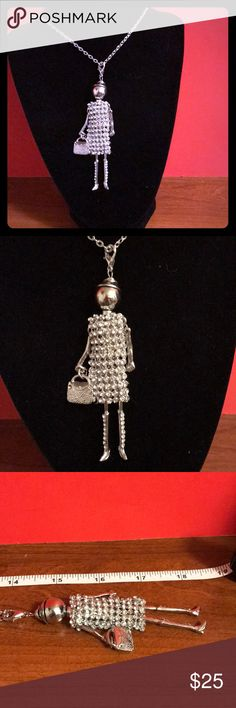 SUPER ELEGANT DOLL NECKLACE Super elegant doll necklace, 13, inch silver chain, silver arms and legs she has on a crystal dress with silver boots with crystal s also has a very elegant purse. Brand new. Lucy & Ethel Jewelry Necklaces