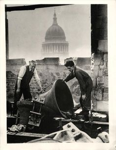 1941- Workmen inspect damaged bells in famed Cheapside church of St. Mary-le-Bow after German air raid. In background is the dome of St. Paul's Cathedral.
