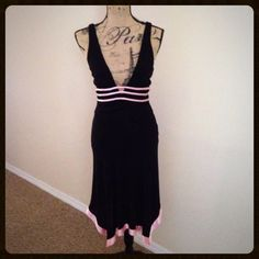 Bebe cocktail dress with pink silk trim One of my favorite dresses of all time! It's time to break out the double-sided tape!!  Bebe cocktail dress, hits below the knee; Has deep, plunging neckline, pink silk contrasting, is fully lined and has back zipper. In great condition, worn only twice. Dry clean only. Measures about 46 in. from top of shoulder to lowest point on the asymmetrical hemline. There are two tiny marks on the bottom pink hem, I will be happy to provide additional photos…