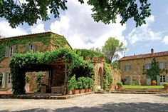 A 17th-century Tuscan farmhouse exudes rustic charm with wood-beamed ceilings and brick archways.
