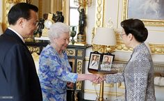 Britain's Queen Elizabeth II (C) receives Chinese Premier Li Keqiang (L) and his…