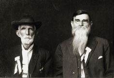 Two members of Hood's Texas Brigade [Civil War] pose for a formal photo during a reunion that took place in Floresville, Texas on October 13, 1915. Pictured left to right are R.V. Arnold of Rockdale, Texas and H. W. Berryman of Cherokee County, Texas. Both gentlemen are wearing their reunion ribbons.