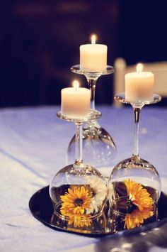 Wine glasses with candles on top and fresh flowers under. Pretty centerpiece.