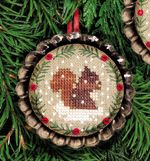 Christmas Tartlet from The Victoria Sampler. Baby fox, baby squirrel and baby bear are playing in the snow, surrounded by a wreath of fir boughs separated by tiny red buttons. They are pictured in shiny metal tart tins, but can also be finished without. Stitch all three Woodland Babies and the matching baby fawn in the 2012 JCS Ornament Issue. Chart retail each US $9.98.  Stores may order wholesale at http://www.victoriasampler.com/