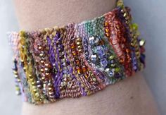 Cuff Bracelet - This loomed cuff incorporates odds and ends of different yarn, fibers and beads. It's a freeform approach to looming; you design as you go, resulting in a modern asymmetrical, textured cuff.