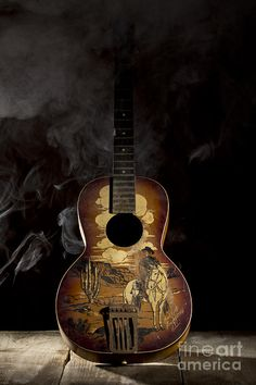 This photograph depicts a studio-lit old timey cowboy guitar in full color set against a black background with wisps of smoke. Guitar Shop, Music Guitar, Whistler's Mother, Painted Guitars, Boat Art, Guitar Painting, Beautiful Guitars, Music Stuff, Musical Instruments