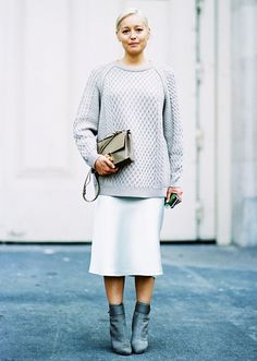 A cable knit sweater is paired with a knee-length skirt, gray boots, and a neutral bag