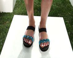 La griffe americana Kate Spade orienta la sua collezione scarpe estiva verso uno stile femminile capace di investire su dettagli audaci che risentono apertamente dalla cifra stilistica anticonvenzi...