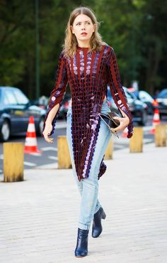 A long sequined top with side-slits is paired with cuffed jeans and black boots.