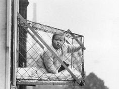 """""""A baby suspended in a wire cage attached to the outside of a high tenement block window. The cages were distributed to members of the Chelsea Baby Club in London who have no gardens""""  - LIFE"""