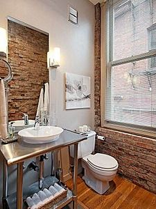 Possible updated mill building bathroom with old brick walls, stainless vanity with white vessel sink and wood floor.