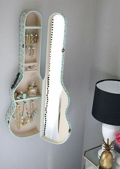 Jewelry holder with mirror on a guitar case.
