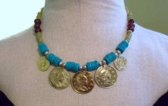 Turquoise, Green, Brown, Silver, Gold are the colors in this statement necklace. Bold gold coins adorn this necklace accented with…