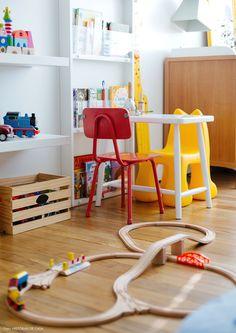 Mesinha e cadeiras coloridas descombinadas na decoração desse quarto infantil.