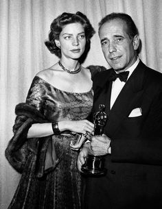 #LaurenBacall & #HumphreyBogart - posing for a portrait at the Academy Awards, held at the RKO Pantages Theater on March 20, 1952, in Los Angeles. Bogart holds the Oscar he won for best actor in John Huston's film 'The African Queen'