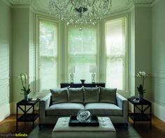 Soft white wooden venetian blinds in a pale green room with contemporary silver and black furniture.