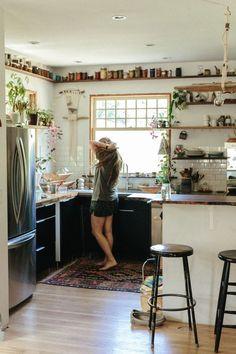 Dans cette petite cuisine bohème : rangement des aliments et des épices dans des bocaux en verre, sur une tablette en hauteur