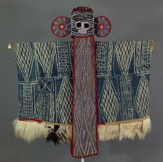 The Bamileke elephant mask and costume wrapper belong to the kuosi society, once a warrior association, now an organization comprising of wealthy and accomplished men.  Today, elephant masks are performed at state ceremonies and funerary festivals of kuosi members, title-holders, and the king.  The elaborate beaded embroidery repeats the isosceles triangle, symbolizing the leopard.  Together, the elephant and leopard imagery link this mask to the powers and abilities of the king.  The masks…
