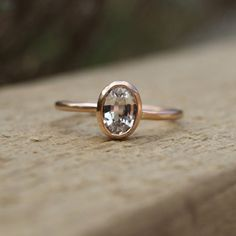 A 7x5mm oval white sapphire set in a handmade 9ct rose gold ring. The delicate band is 1.5mm wide and the sapphire is 0.75ct. Sapphires are a