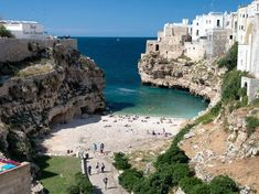 Polignano A Marel, Italy rises out of a cliff face on the Adriatic Sea. Boasts a beach with warm turquoise waters, flanked on either side by cliffs.
