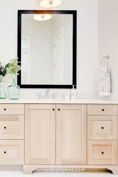 Warm white oak vanity cabinets in the master bathroom of the Restoration home designed and built by Clark & Co. Homes bring warmth to this bright white space. Black framed mirrors and small sweet cabinet hardware add contrast, creating a modern farmhouse look in this bathroom design. Modern Traditional, Traditional Bathroom, Traditional House, Custom Home Builders, Custom Homes, Garage Floor Plans, Framed Mirrors, Floor Plan Layout, Classic Bathroom