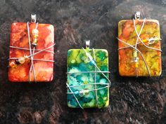 Alcohol ink on game tiles, such as rummy-0 or domino pieces, with wire wrapping, beads and glue-on pendant bails for necklace hanging.