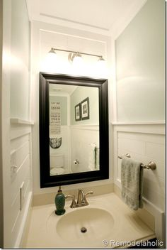 half bath makeover with a planked wall  and framed mirror. Details at remodelaholic.com.
