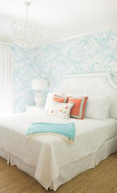 Stray Dog Designs Landon Chandelier illuminates an aqua bedroom filled with a white headboard accented with blue piping, lining a wall clad in blue leaf print wallpaper, accented with orange pillows and an aqua blue throw.