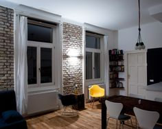 Raw brick wall, an orignal in the century-old building. Eames replica chairs…