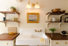 Cast iron farm sink inset cabinets open shelving gold accents wood countertops