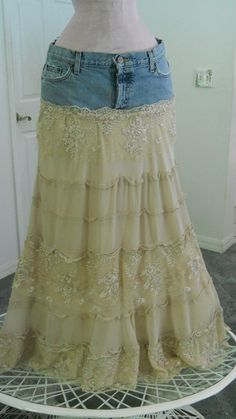 "To make the """"Isabelle"" jean skirt,  took a pair of faded, destroyed jeans with cool tatters, rips and holes to form a yoke for the top.Next, made a skirt bottom out of tiers of beige ecru silky crepe and lined it with a satiny beige lining.Then, I made tiers of exquisite vintage lace and tattered the lace to complement the destroyed denim."